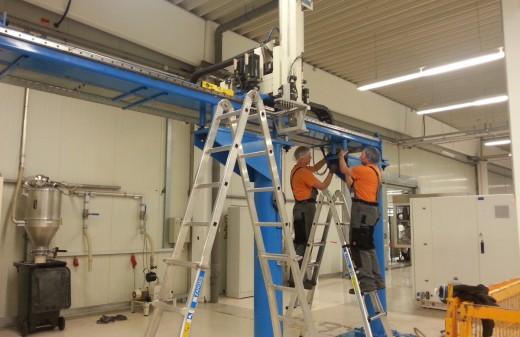 Zwei Mitarbeiter der Seidel-Industriemontage GmbH stehen auf Leitern und montieren ein Portal