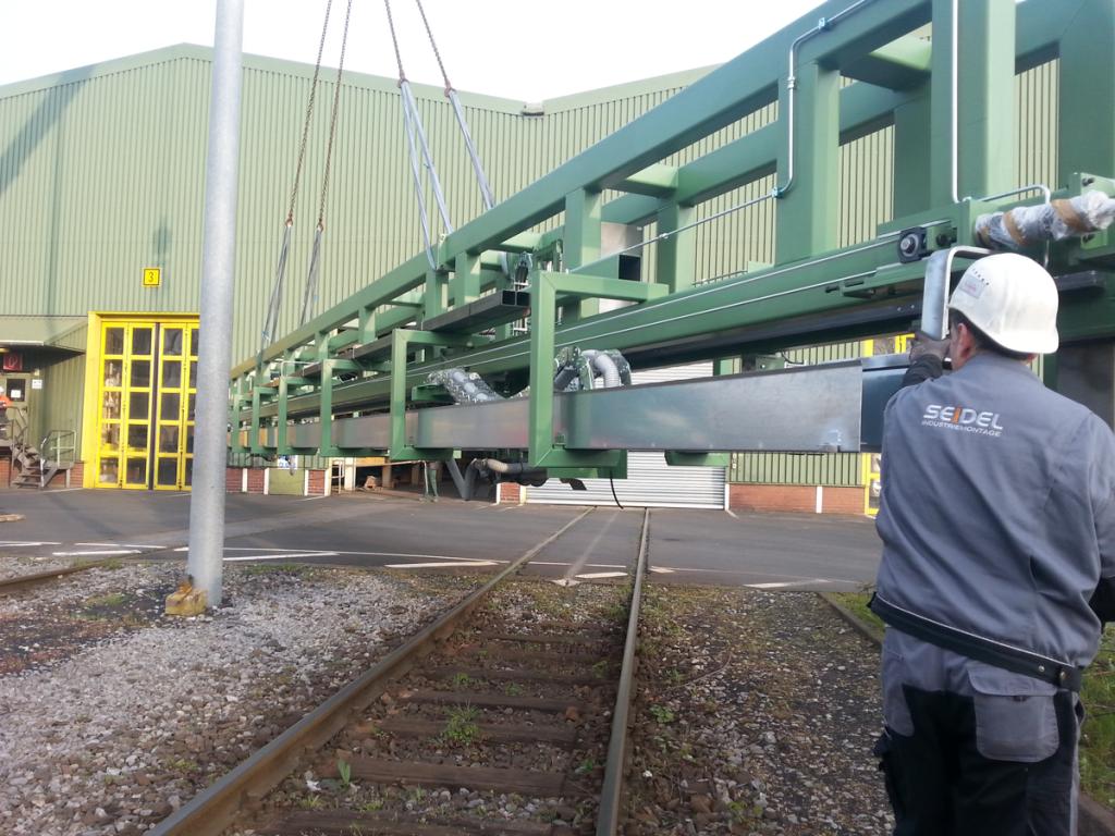 Mitarbeiter von Seidel Industriemontage bewegt ein 18 Meter langes Portal mit Autokran