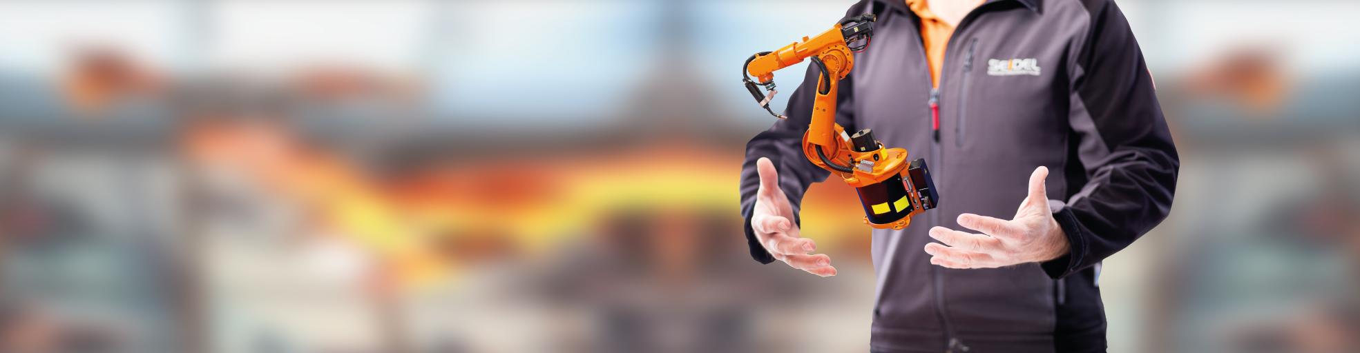 Seidel Industriemontagen Mitarbeiter mit schwebendem Roboter zwischen den Händen